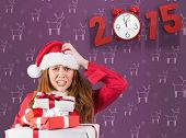 Festive stressed redhead holding gifts against purple reindeer pattern