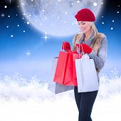 Blonde in winter clothes with shopping bags against white clouds under blue sky