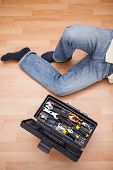Man legs with toolbox on floor at home in the living room