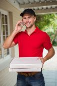 Happy pizza delivery man on the phone in front of house