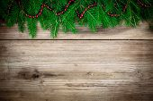 stock photo of candy cane border  - Pine tree border with red garland on old rustic wooden background - JPG