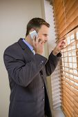 Businessman peeking through blinds while on call in office