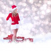 Pretty santa girl presenting with hand against light glowing dots design pattern