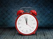 Alarm clock counting down to twelve against dark grimy room