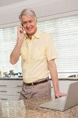 Senior man using his laptop on the phone at home in the kitchen
