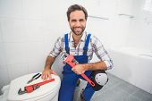 Plumber smiling at the camera in the bathroom