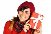 Smiling brunette in red hat holding gift on white background