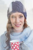 Pretty redhead in warm clothing holding mug seen through glass window