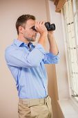 Man looking through a binoculars at home