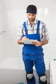 Plumber taking notes on clipboard in the bathroom