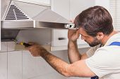 Handyman fixing the oven in the kitchen