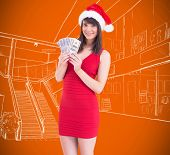 Festive brunette in red dress showing her cash against orange vignette