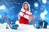 Pretty santa girl holding gift against christmas scene with gifts and candy canes
