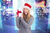 Festive blonde holding christmas gift against glittering screen in urban setting