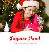 Little girl opening a gift at christmas against joyeux noel