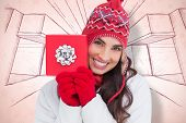 Festive brunette in winter clothes showing red gift against snowflake wallpaper pattern