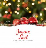 Joyeux noel against focus on red christmas baubles