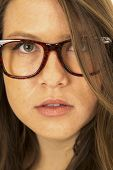 Serious Woman Peering Through Her Hair Wearing Glasses