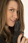 Close-up Portrait Of A Woman Holding A Pistol With A Smirk On Her Face