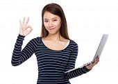 Woman use of notebook and ok sign