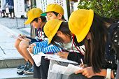 KYOTO, JAPAN-OCT 24,2014: Japanese school children with yellow caps do homework  in  Kyoto street on Oct 24, 2014, Japan.