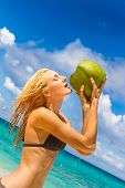 young beautiful woman drinking fresh coconut milk, tropical sand beach, sky and sea background