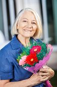 Portrait of happy senior woman holding flower bouquet at nursing home yard