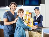 Portrait of expectant couple buying popcorn and drink from female seller at cinema concession stand