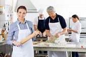 Portrait of confident female chef holding rolling pin while colleagues preparing pasta at commercial kitchen