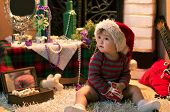 picture of santa baby  - Funny baby in Santa hat sitting on the carpet with a cup in her hands  - JPG