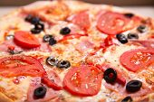 Close-up shot of Italian pizza with ham, tomatoes and olives, selective focus