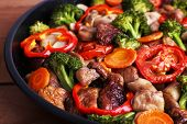 Braised wild mushrooms with vegetables and spices in pan close-up