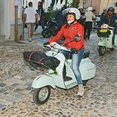 Biker Woman Riding A Vintage Italian Scooter Vespa