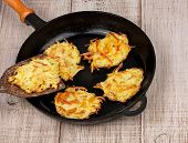 Golden potato fritters on old cast iron frying pan