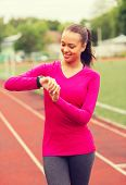sport, fitness, technology, healthcare and people concept - smiling young woman with heart rate watch on track outdoors