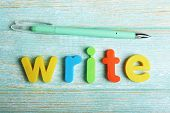 Write word formed with colorful letters on wooden background