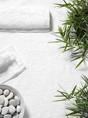 Bamboo leaves and a white towel with lotion and pebbles