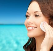 beauty, people and health concept - beautiful smiling woman cleaning face skin with cotton pad over blue sea and sky background