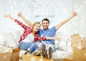 moving, home and couple concept - smiling couple showing thumbs up and waving hands on sofa in new home