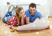 repair, building, renovation and people concept - smiling couple looking at blueprint at home