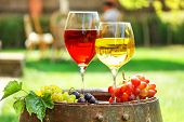 Glasses of wine on old barrel with iron rings in a garden