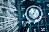 Financial analysis, audit or accounting - Stethoscope over a calculator and dollar bills toned in blue