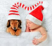 Newborn baby and puppy wearing Christmas Santa hats.
