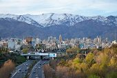 stock photo of tehran  - Tehran skyline and greeneries in front of snow covered Alborz Mountains as viewed from atop of Nature Bridge - JPG