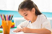 foto of hispanic  - Cute little hispanic girl writing at school