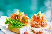 stock photo of antipasto  - Fresh homemade crispy Italian antipasto called Bruschetta topped with tomato - JPG