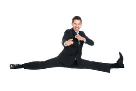 picture of karate-do  - Full length portrait of young businessman doing splits while gesturing over white background - JPG