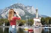 picture of memento  - Tourist young woman is taking picture of Lecco lake - JPG