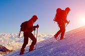 pic of mountain-climber  - climbers at the top of a pass with backpacks meeting the sunrise in the mountains - JPG