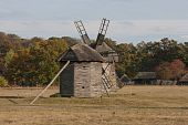 Autumnal Country Scenery. Two Wooden Windmills  In The Foreground.